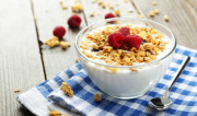 Muesli with yogurt and raspberries in a bowl on a brown wooden background